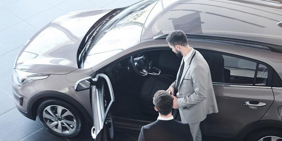 Businessman standing near the new car with salesman consulting him in car salon