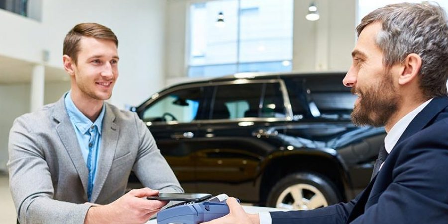 Portrait of successful young man buying brand new luxury car in showroom paying via smartphone sitting across table from mature salesman