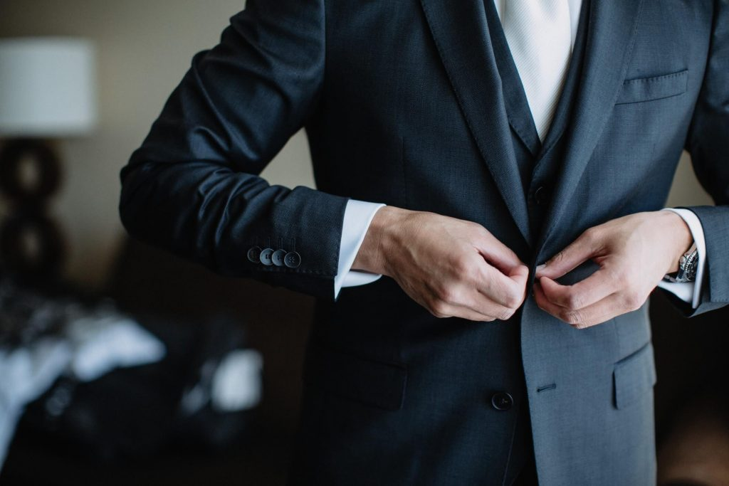 diverse-young-man-getting-ready-and-putting-on-his-suit-and-tie-formal-evening-wear-business-attire_t20_koe3aE
